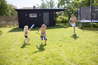 Siblings playing with water guns in backyard - FOLF01341