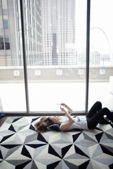 High angle view woman using smart phone while lying on carpet by window at home - CAVF28890