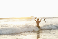 Teenager with surfboard wading in sea at Costa Rica - FOLF01359