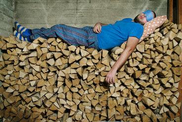 Man sleeping on pile of firewood - FOLF01449