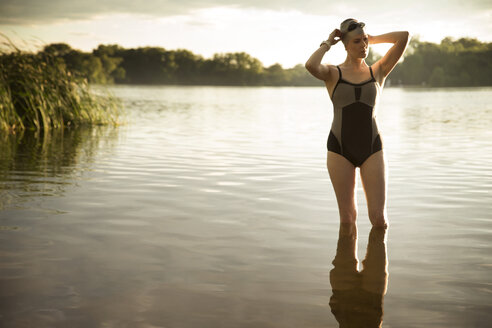 Swimmer wearing swimming goggles while standing in lake - CAVF29140