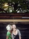 Happy sisters enjoying against wooden wall - CAVF29158