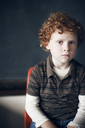 Portrait of boy sitting in front of blackboard at school - CAVF29194