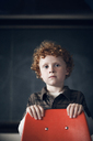 Portrait of boy standing behind chair at classroom - CAVF29197