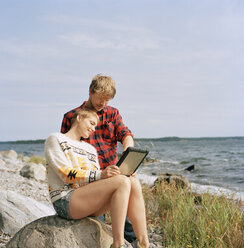 Couple using tablet pc at beach - FOLF01584