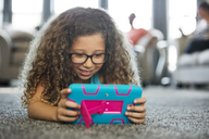 Girl playing handheld video game while lying on carpet at home - CAVF29327