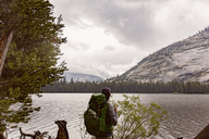 Hiker carrying backpack standing by river at Yosemite National Park against cloudy sky - CAVF29363