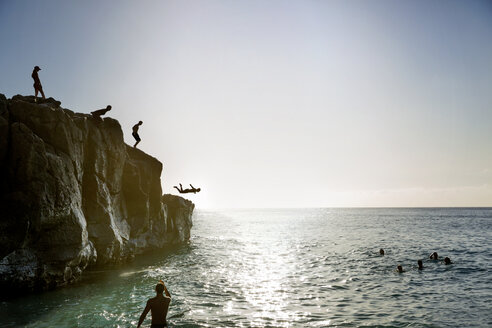 Friends jumping from cliff to sea against sky - CAVF29369