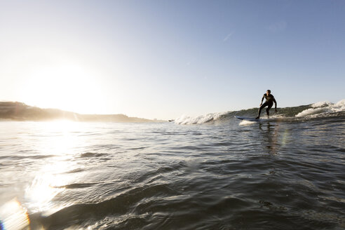 Man surfing on sea against clear sky during sunset - CAVF29402