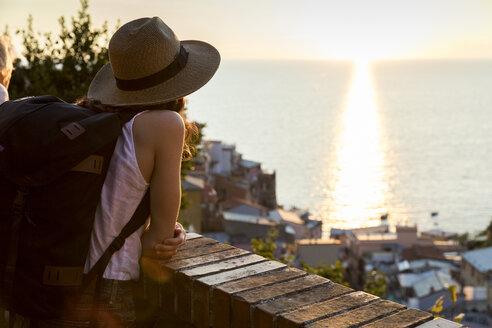 Side view of female hiker looking at sunset view while standing on balcony - CAVF29417