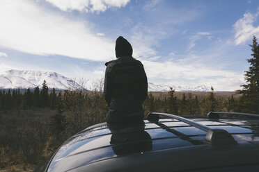 Rear view of thoughtful woman sitting on car roof at Denali National Park against snowcapped mountains - CAVF29426