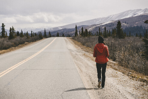 Rear view of woman walking by country road at Denali National Park - CAVF29429