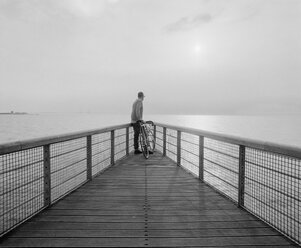 Black and white picture of man looking at view on pier - FOLF01964