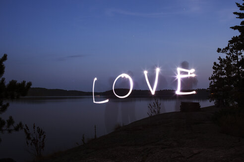 Love text made from light painting over lakeshore against blue sky at dusk - CAVF29589