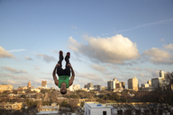 Full length of man jumping upside down against sky in city - CAVF29649