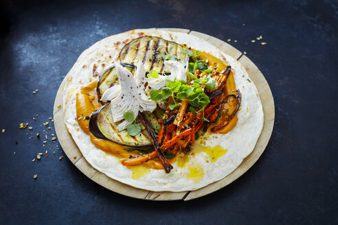 Pulled Chicken Wrap, carrot, grilled aubergine, curry hummus and herbs on chopping board - KSWF01882