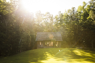 Log cabin on field against trees during sunny day - CAVF29705