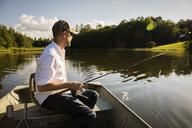 Man fishing while sitting in rowboat on lake - CAVF29711