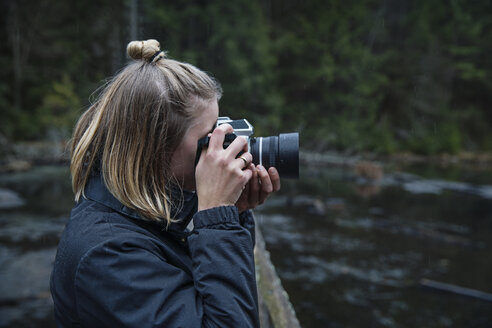 Side view of woman photographing with camera against river - CAVF29762