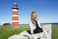 Girl sitting on rock with lighthouse in background - FOLF02178