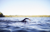 Woman swimming in lake against clear sky - CAVF29969