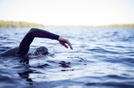 Cropped image of woman swimming in lake against sky - CAVF29972