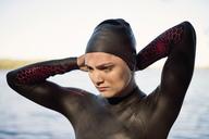 Thoughtful female swimmer wearing swimming cap at lakeshore - CAVF29981