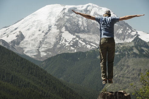 Man jumping with arms outstretched against Mount Rainier - CAVF30098