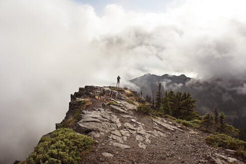 Man standing on cliff against cloudy sky - CAVF30107