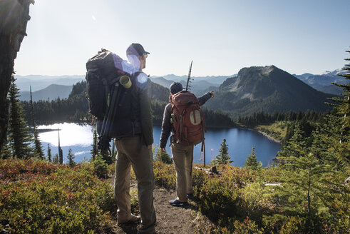 Male friends hiking on mountain against lake - CAVF30116