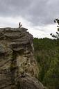 Low angle view of man and dog standing on cliff against cloudy sky - CAVF30146