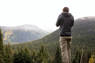 Rear view of man standing on mountain against clear sky - CAVF30206