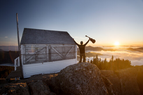 Rear view of man holding guitar while standing by log cabin on mountain during sunset - CAVF30218