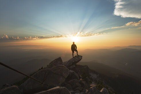 Man standing on rock at cliff against sky during sunset - CAVF30236