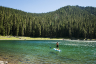 Man riding paddalboard on lake against forest - CAVF30326