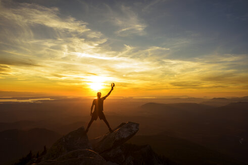 Silhouette hiker holding cap with hand raised while standing on top of mountain during sunset - CAVF30332
