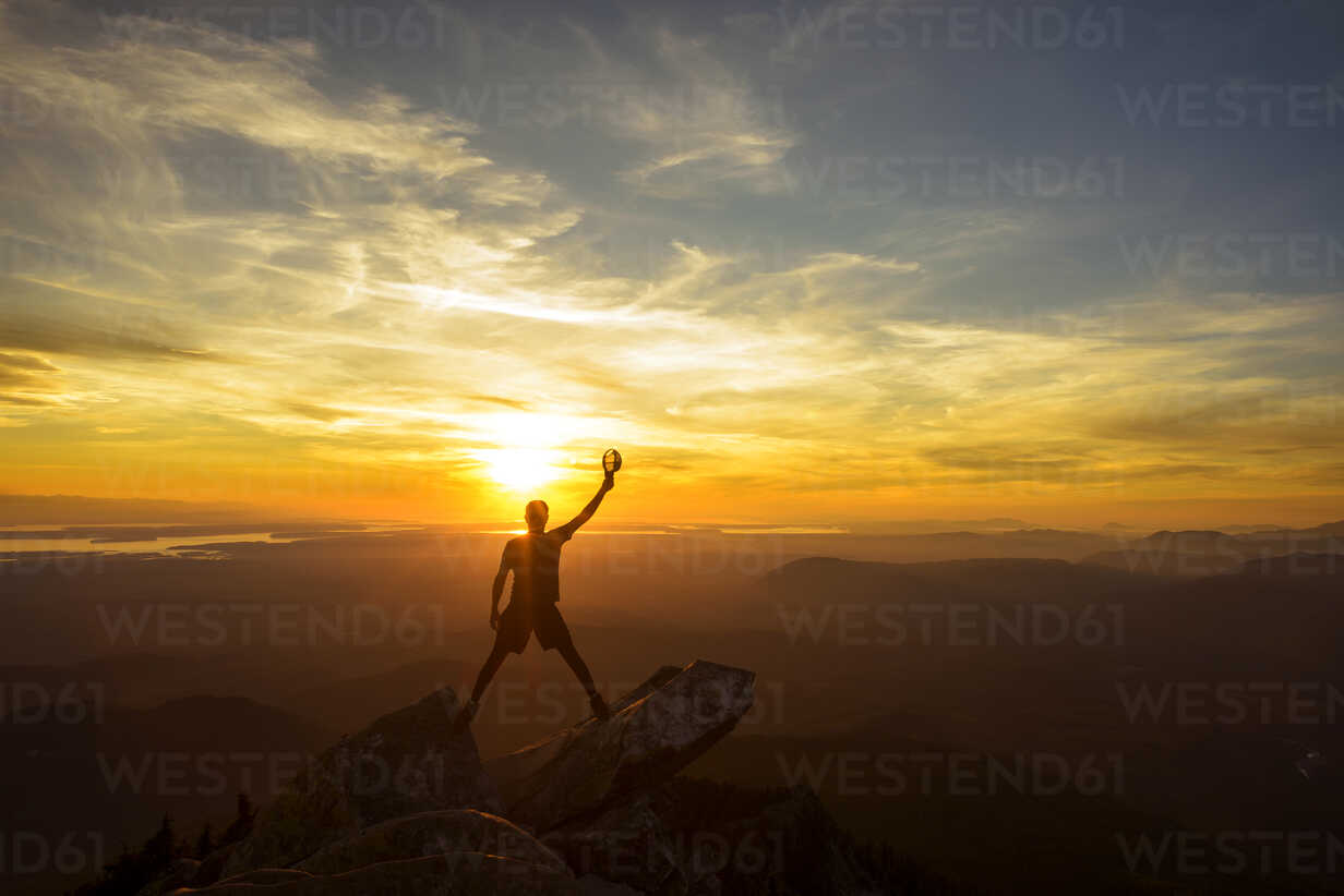 Silhouette hiker holding cap with hand raised while standing on top of mountain during sunset - CAVF30332 - Cavan Images/Westend61