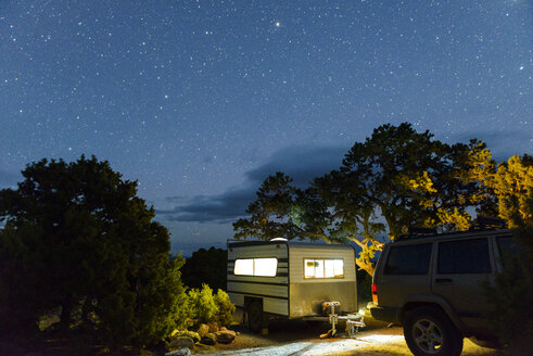 Car and travel trailer parked against star field - CAVF30389