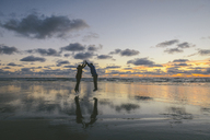 Side view of couple jumping together at Long Beach against cloudy sky during sunset - CAVF30402