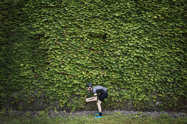 Side view of man bending against ivy covered building - CAVF30435