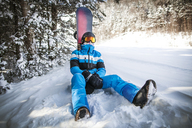 Man with snowboard relaxing on snow covered field - CAVF30546