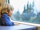 Little boy looking through window in train - FOLF02553