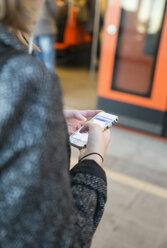 Young woman using smartphone on Helsinki Metro - FOLF02559