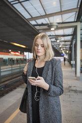 Young woman using smartphone on Helsinki Metro - FOLF02562