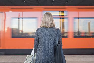 Rear view of woman standing on Helsinki Metro - FOLF02565