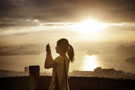 Woman photographing while standing at observation point during sunset - CAVF30605