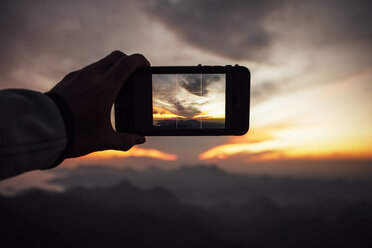 Cropped image of man photographing cloudy sky through smart phone during sunset - CAVF30620