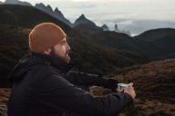 Thoughtful man holding mug while sitting on mountain - CAVF30623
