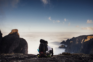 Rear view of backpacker sitting on mountain against sky - CAVF30626