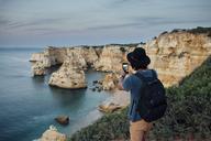 Hiker photographing mountains by sea through smart phone at Praia da Marinha - CAVF30644